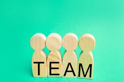Four wooden people with the inscription `team`. group work. teamwork. achievement of goals, corporate spirit. cohesion in the team. Workers stock photos