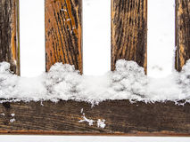 Four wooden rungs or spokes covered with snow. Detail of weathered wooden bench covered in snow, four rungs or spokes, geometrical vertical and horizontal lines Stock Photo