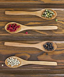 Four wooden spoons with color peppers Stock Images