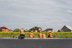 Four workers resting on the road construction site with a houses behind them. stock photo