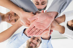 Four workers stacking hands together Royalty Free Stock Photography
