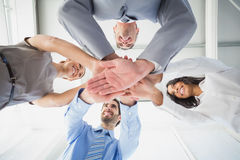 Four workers stacking hands together Stock Photography