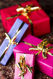 Four Wrapped Gifts with Golden Bows. Presents packed for any occasion. Two packets in magenta, one in blue and one in crimson red. All tied with golden ribbons Stock Image