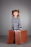 Four-year beautiful girl. Has control over two old suitcases on a gray background Royalty Free Stock Photos