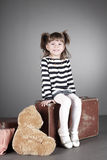 Four-year beautiful girl sits on an old suitcase Royalty Free Stock Image