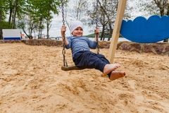A four-year boy riding on a swing royalty free stock image
