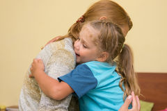The four-year daughter hugging her mother sitting on the bed in room Stock Photo