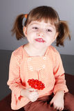 Four-year girl with the big sugar candy Stock Photo
