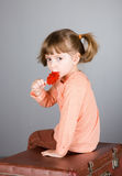 Four-year girl with the big sugar candy Stock Photos
