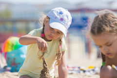 Four-year girl builds a sand castle on the beach Royalty Free Stock Images