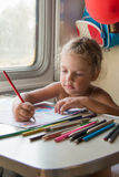 Four-year girl drawing with pencils at a table in a train Stock Photos