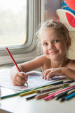Four-year girl draws pencil drawing of a table in a second-class train carriage Royalty Free Stock Image