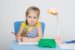 Four-year girl draws pencils and funny looks in picture Royalty Free Stock Photo