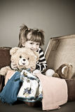 Four-year girl joyfully sits in an old suitcase Royalty Free Stock Image