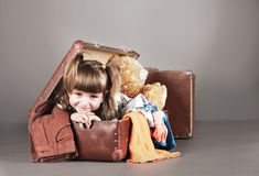 Four-year girl joyfully sits in an old suitcase Stock Photo