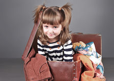 Four-year girl joyfully sits in an old suitcase Stock Images
