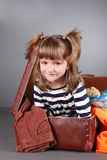 Four-year girl joyfully sits in an old suitcase Stock Image