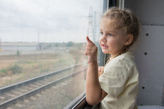 Four-year girl shows a finger on something from the window of a train car. Four-year girl looking out the window with the bottom side of the shelf in the second royalty free stock photos