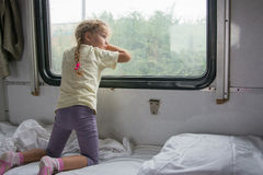Four-year girl on the side of the shelf of the train looking out the window Stock Photos