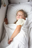 Four-year girl sleeping on the bottom shelf in a train Royalty Free Stock Photo