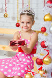 Four-year girl stretches forward a little gift sitting snowy Christmas trees Royalty Free Stock Image