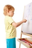 Four-year old boy drawing picture on easel Stock Images