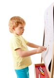 Four-year old boy drawing picture on easel Royalty Free Stock Photo
