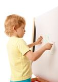 Four-year old boy drawing picture on easel Stock Image