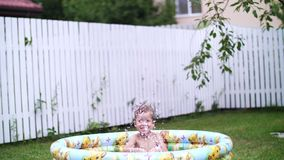 A four-year-old boy lies in a children`s inflatable pool, splashing water, smiling. Nearby float toys. In the garden, in stock video