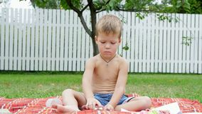 A four year old boy playing with plasticine in the garden, sitting on a blanket, a coverlet, on grass, lawn, in the. Summer stock footage