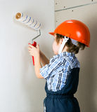 Four year old boy in protective helmet construction painstakingl Stock Photos
