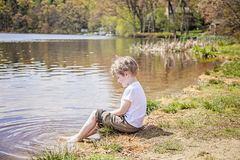 Boy sitting on shore of lake. Four year old boy sitting on the shore of lake on a spring day with his feet in the water stock images
