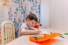 A four year old child draws with colored pencils royalty free stock images