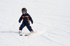 Four year old child skiing alone Stock Images