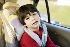 Four year old disabled boy in carseat. Four year old boy with cerebral palsy sitting in carseat Stock Photography