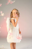 Four year old girl as angel. Cute little girl wearing a white dress and feathered angel wings, standing as pink feathers fall around her Royalty Free Stock Photography