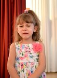 The four-year-old girl cries in the kindergarten hall stock photo