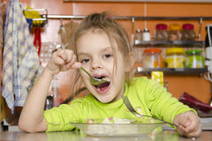A four year old girl eats with a fork and spoon sitting at the table in the kitchen Royalty Free Stock Image