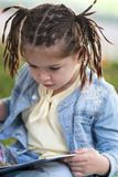 Four-year-old girl with pigtails in a blue jacket and a yellow T. Shirt looking at a book on a bench under a tree in the park Royalty Free Stock Photography
