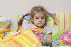 Four-year-old girl with pigtails lying in bed under the blanket Stock Image