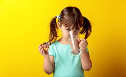 Four-year-old girl in a turquoise t-shirt eat donuts and drink chocolate milk. The girl`s hair is tied in tails. Yellow background stock photo