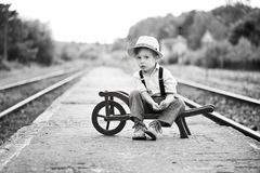 Monochrome portrait of cute boy wearing in retro style sitting on railway station and is waiting for something. Four year old sad boy, dressed in retro style Stock Photo