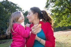 Mother and litlle child in nature eating peach Stock Photos