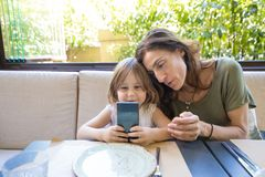 Little girl watching mobile with woman in restaurant. Four years age blonde girl with mobile in her hands, smiling and watching with women mother sitting in Royalty Free Stock Images