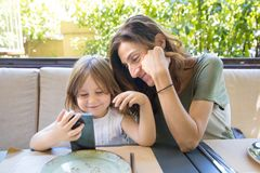 Little child and mother watching smartphone in restaurant Royalty Free Stock Photo