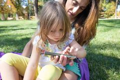 Little girl touching mobile screen of woman sitting in park Stock Image