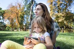 Little girl watching mobile sitting on woman legs in park. Four years age blonde girl watching smartphone, sitting and hugging her mother on green grass in park Stock Photos