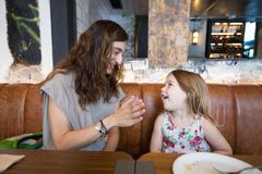 Little girl laughing with mother sitting in restaurant Stock Images