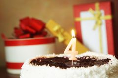 Four years birthday. Cake with burning candle and gifts Stock Photo