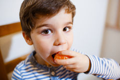 Four years boy eat a mandarin. 4-years boy eat a mandarin with great pleasure stock images